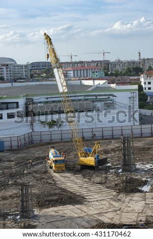 Truck crane and concrete mixer truck working at the construction site - stock photo