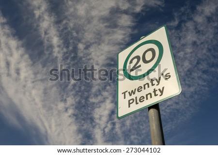 """""""Twenty's Plenty"""" sign with cloudy blue sky.  - stock photo"""
