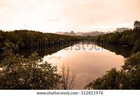twilight time , low light along the mangrove forest along the river to the end of view at the mountain  - stock photo