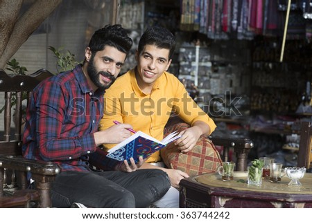 Two Arabic models looking young guys concentrated on a book at cafe shop concept theme in Cairo Egypt in middle east Africa   - stock photo