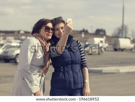Two Beautiful urban woman taken picture of herself, selfie. - stock photo