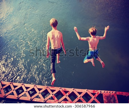 two boys jumping of an old train trestle bridge into a river toned with a retro vintage instagram filter effect app or action - stock photo