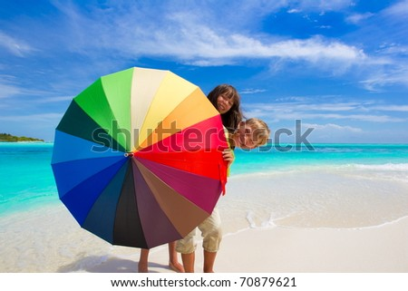 Two children hiding behind a colorful umbrella on the beach - stock photo