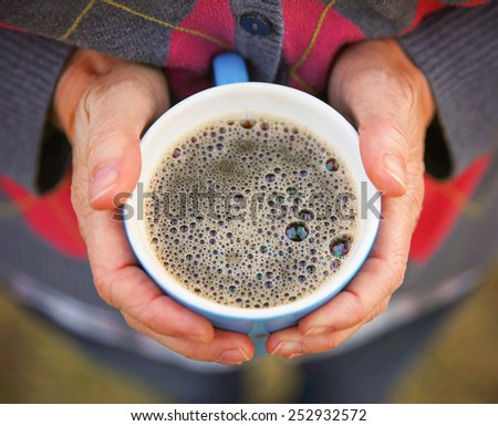 two hands keeping warm, holding a hot cup of tea or coffee  - stock photo