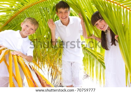 Two happy brothers and their sister dressed in white, standing within palm fronds on a beach in the Maldives. - stock photo
