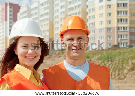 two happy builders in hardhat works on the building site - stock photo