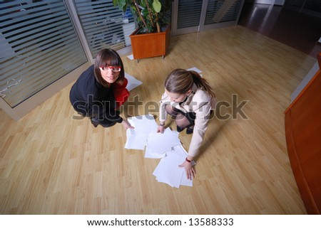 .two happy businesswoman throw papers in office
