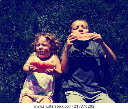two kids eating watermelon toned with a retro vintage instagram filter effect - stock photo