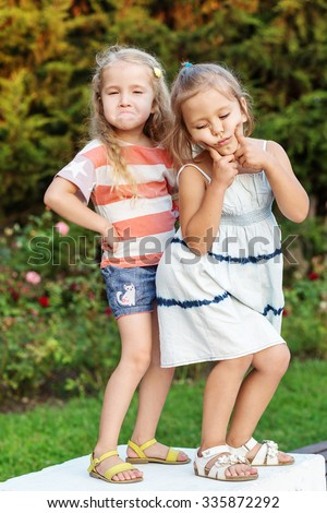 two little funny funny girls posing in the summer