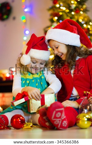 Two little girls in the Santa hat open Christmas present under the Christmas tree - stock photo