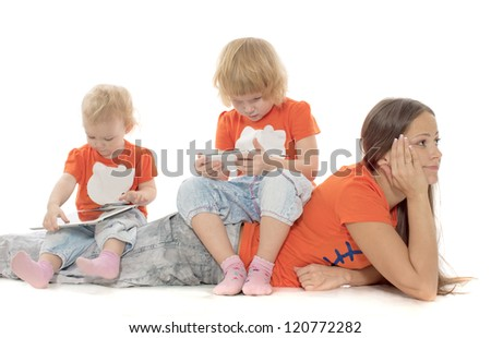 Two little girls sit on the woman with phone and a computer - stock photo
