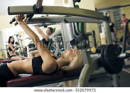 2 two man 3 woman with long blond brunette hair sitting smiling face Portrait of three young adult Girls do exercise for legs and hands. in fitness gym on mirror with reflection and window background - stock photo