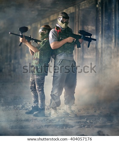 Two paintball shooters with paintball guns  - stock photo