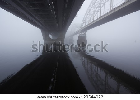 Two parallel bridges over the misty river. - stock photo