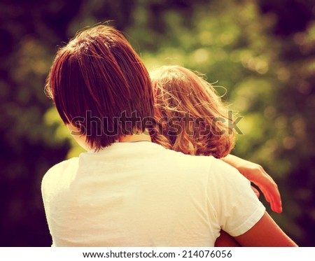 two people hugging outside toned with a retro vintage instagram filter  - stock photo
