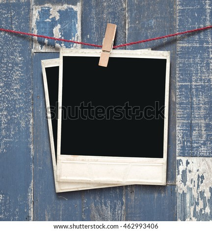 two photos hanging on wooden background.