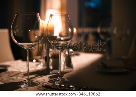 two spare glasses and candle light at the restaurant  - stock photo