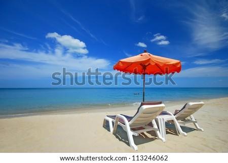 two sunbed on the beach setup on the Peaceful beach  with orange Umbrella - stock photo