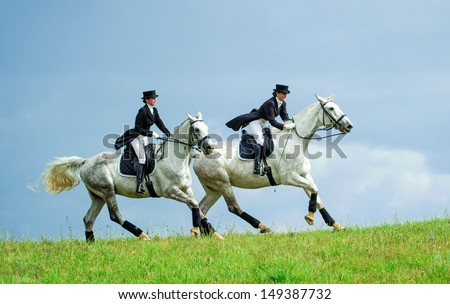 Two women riding horses on the top of the hill. Equestrian sport - dressage. - stock photo