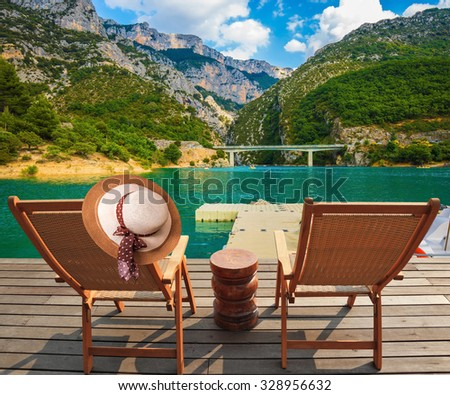 Two wooden chairs and straw hat on the platform at lake Verdon. Travel to Provence - stock photo