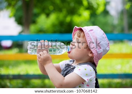 two-year child drinks from plastic bottle in park