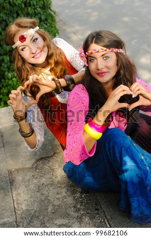 Two young beautiful funny girls of hippie sit in the street - stock photo
