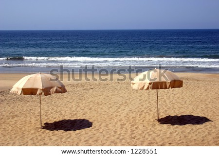 2 umbrellas in the sand overlooking the ocean - stock photo