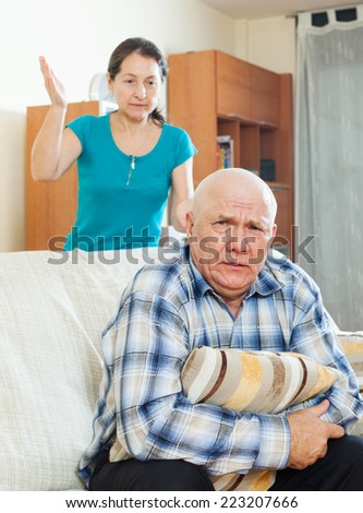 Unhappy senior man with angry wife at home - stock photo