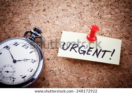 """""""Urgent!"""" written on a post note and hanged on the cork-board with an old pocket watch. - stock photo"""