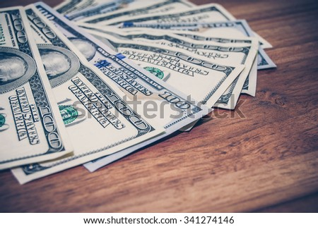 100 US dollars banknotes on wooden background. tinted photo