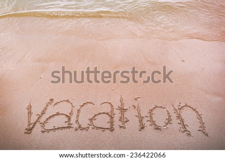 """""""Vacation"""" ; written in the sand on the beach (vintage tone) - stock photo"""
