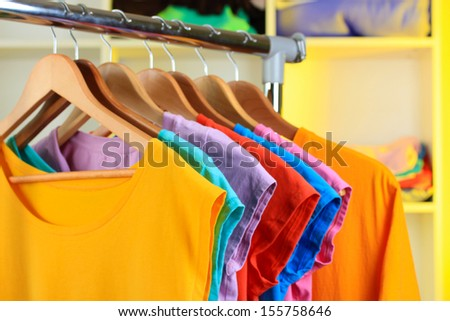 Variety of casual t-shirts on wooden hangers on shelves background - stock photo