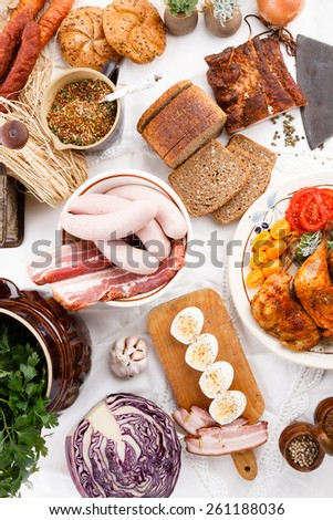 various meal type like polish sausage smoked bacon pork meat roasted chicken leg bread herb boiled egg on tablecloth - stock photo