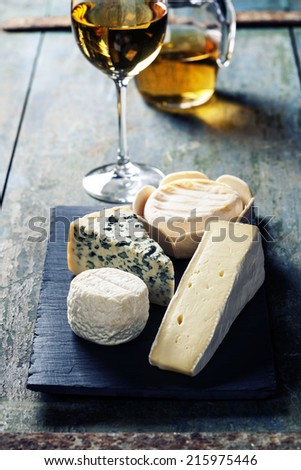 Various types of cheese and white wine on wooden background - stock photo