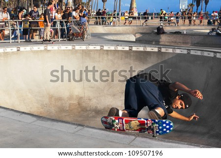 VENICE-AUG 4: A skateboarder skates sideways along the edge of a bowl while a crowd watches him at the Venice Skatepark in Venice, CA on Aug. 4, 2012.  - stock photo