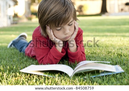 Very cute 7 year old boy lying on the grass reading a kids book - stock photo