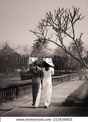 Vietnamese girls with Ao Dai in Hue, Vietnam. Ao dai is famous traditional costume for woman in VIetnam. - stock photo