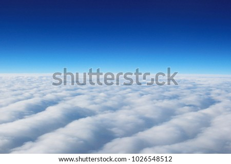 view from the window of an airplane flying in the clouds.