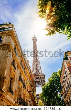 View of the Eiffel Tower from a street of Paris in a sunny summer day. Flare because of the sun  - stock photo
