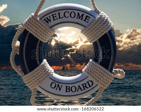 view on the sailing ships in sunset through blue safe belt with welcome on board sign - stock photo