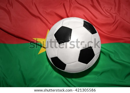 vintage black and white football ball on the national flag of burkina faso