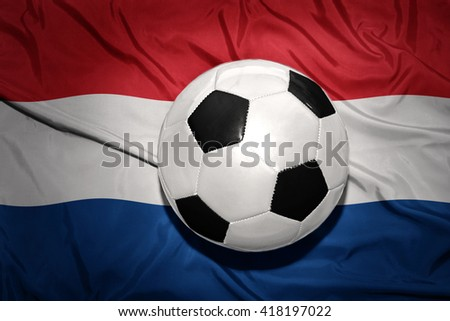 vintage black and white football ball on the national flag of netherlands, dutch, amsterdam, - stock photo