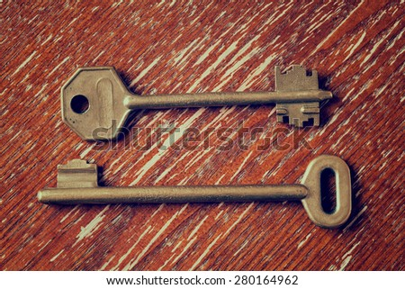 Vintage keys on a wooden table - stock photo