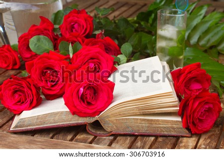 vintage open book  on table with red roses - stock photo