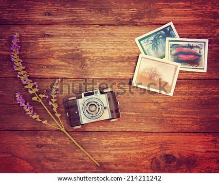 Vintage photo camera on a wooden table with some snapshots and a flower toned with a retro vintage instagram filter effect  - stock photo