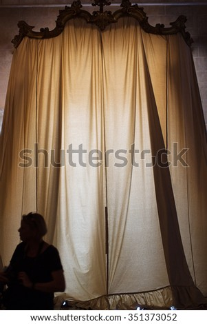 Visitor to a church in Lucca, silhouetted against  the very large curtains at the church entrance
