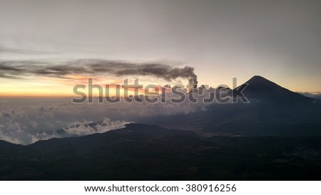 Volcano - Volcan Agua erupting near Antigua, Guatemala at sunset with the smoke trailing across the dusk sky - stock photo