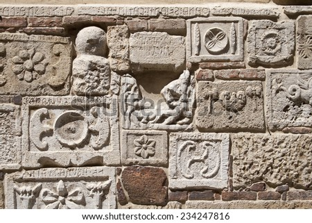 Wall with antique stones from the classical greek architecture, with historical inscriptions some hundred years before Christ. (Was seen in Italy.) - stock photo