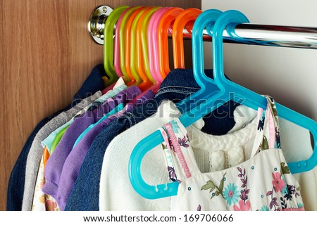 wardrobe with baby c�lothes on  hangers  - stock photo