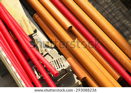 water, fiber optic and sewer pipes for men construction workers  to repair  the street at city - stock photo